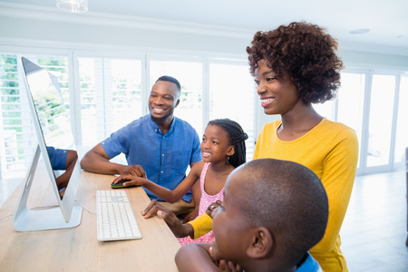 family  room: Happy family using computer in living room at home