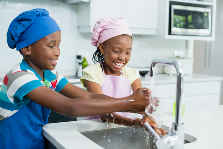 Smiling siblings washing hand in kitchen at home
