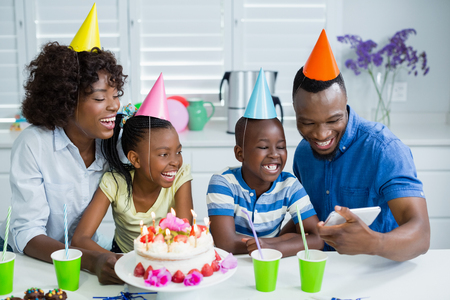 domicile: Family looking at picture while celebrating birthday party at home
