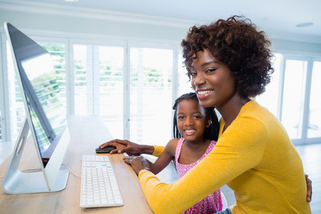Portrait of mother and daughter using computer in living room at home