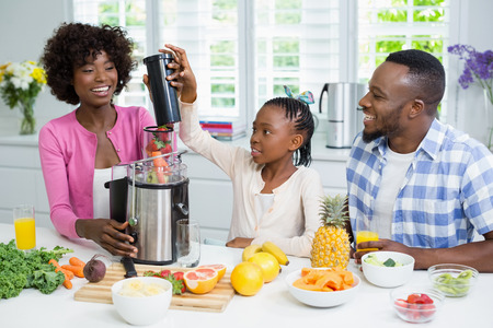 Smiling parents and daughter preparing strawberry smoothie in kitchen at home
