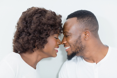 Couple romancing face to face in bedroom at home