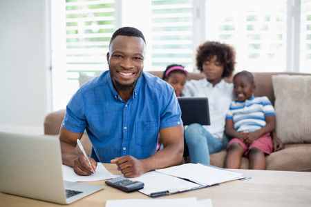 figuring: Portrait of smiling man calculating bills while his wife and kids sitting on sofa
