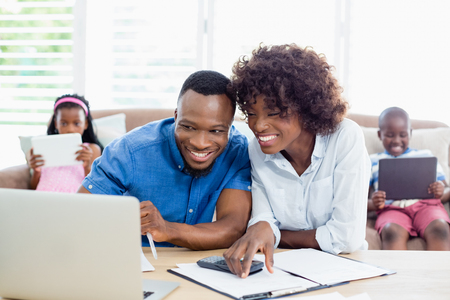 household money: Couple sitting at table and calculating bills at home