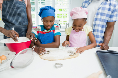 Parents and kids preparing food in kitchen at home Stock Photo