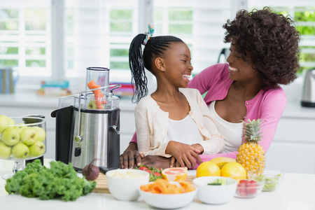Smiling mother and daughter interacting in kitchen at home