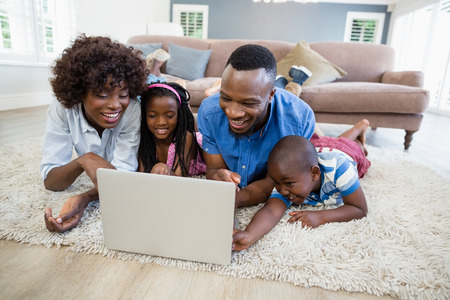 family  room: Happy family using laptop in living room at home Stock Photo