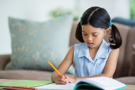 自宅の居間で宿題をする気配りのある女の子 写真素材