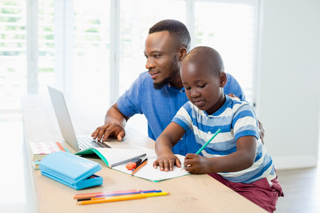 Father using laptop and son doing his homework in living room at home