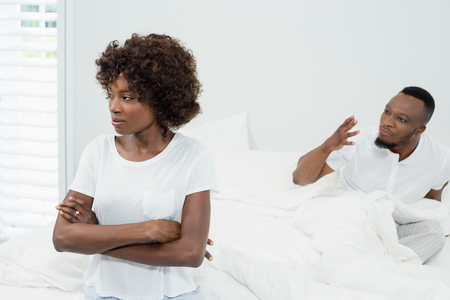 Couple arguing with each other in bedroom at home