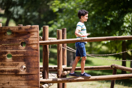 Boy walking on a playground ride in park on a sunny day