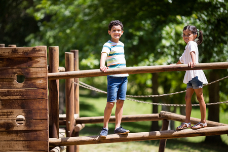 Kids standing on a playground ride in park on a sunny day