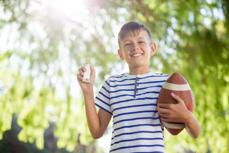 Boy holding asthma inhaler and a rugby ball on a sunny day Stock Photo