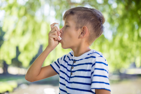 Young boy using asthma inhaler in park