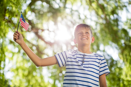 Boy holding small american flag in a park Stock Photo