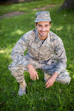 Portrait of young soldier smiling in park