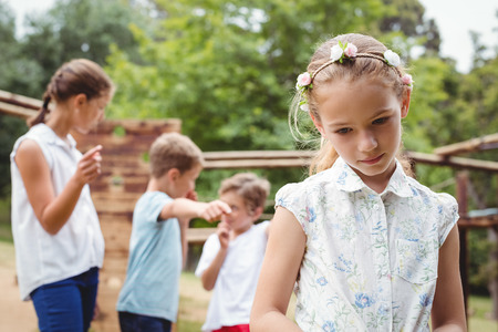 Upset girl with friends gossiping in background at park