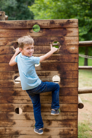 Boy climbing on a playground ride in park on a sunny day Stock Photo