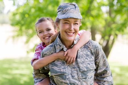 公園で彼女の娘におんぶを与える幸せな女性兵士 写真素材
