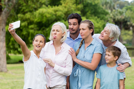 Multi-generation family taking a selfie on a mobile phone in park