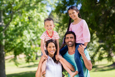 Portrait of parents carrying their children on shoulder in park on a sunny day