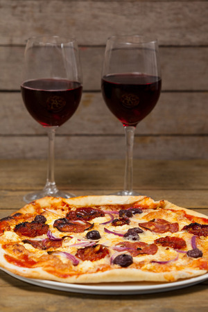 Delicious pizza with glasses of red wine on wooden plank