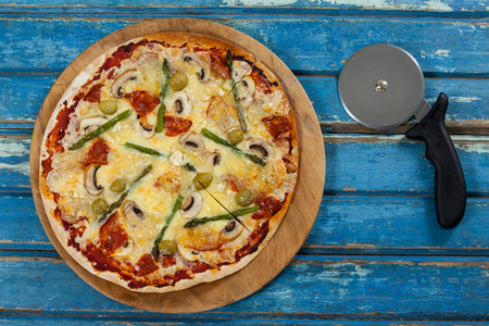 pizza cutter: Overhead of delicious pizza served on pizza tray with cutter on wooden plank