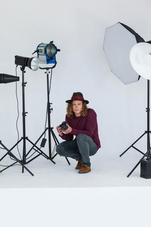 Portrait of photographer holding digital camera in the photo studio