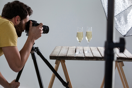 Male photographer photographing champagne glasses in studio