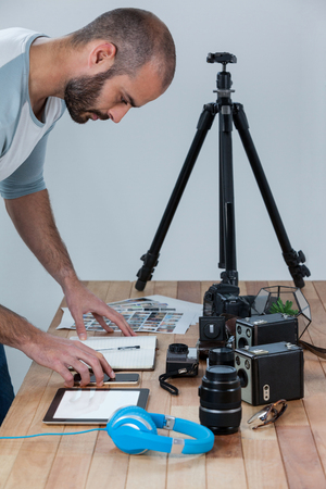 Male photographer working at desk in studio