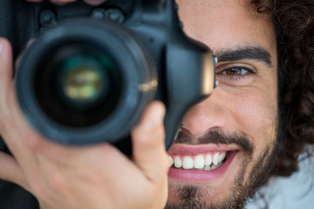Close-up of happy male photographer with digital camera in studio