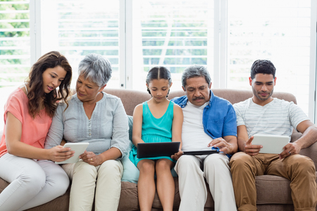 family  room: Multi-generation family using digital tablet in living room at home Stock Photo
