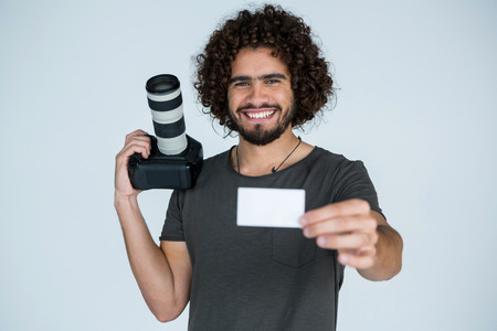 visiting card: Portrait of male photographer showing visiting card in studio