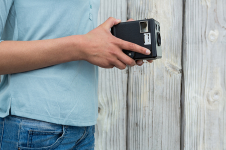 Mid section of female photographer holding old fashioned camera against wooden background