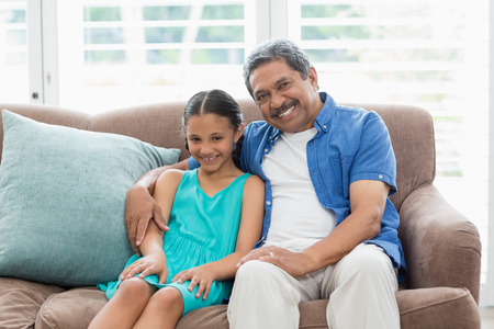 Grandfather and granddaughter sitting on sofa in living room at home Stock Photo