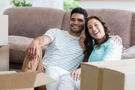 Happy couple sitting with arm around in living room at home Stock Photo
