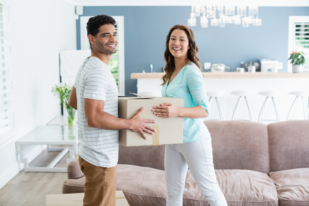 Portrait of couple holding card boxes in living room at home Stock Photo