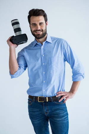 Portrait of happy photographer holding a camera in the studio Stock Photo