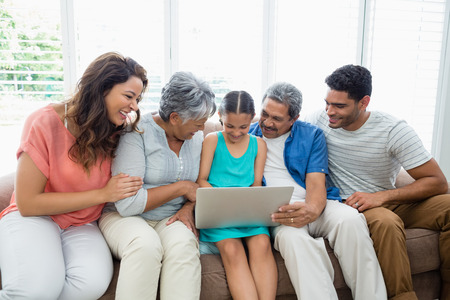 family  room: Happy multigenration family using laptop in living room at home