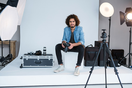 Portrait of male photographer standing in studio