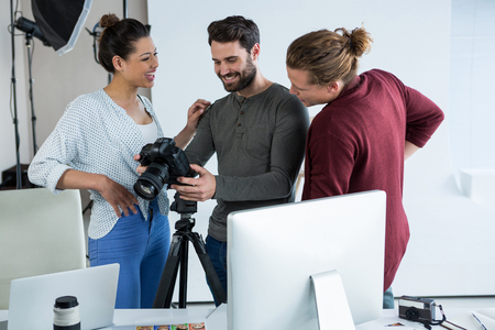 Photographers and model reviewing captured photos in his digital camera at studio