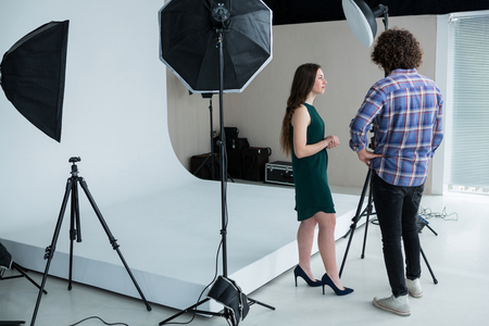 Photographer and female model reviewing captured photos in digital camera at studio