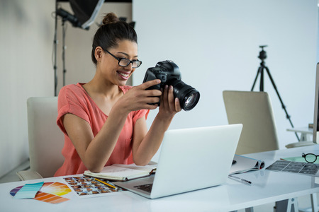 Female photographer reviewing captured photos in her digital camera at studio