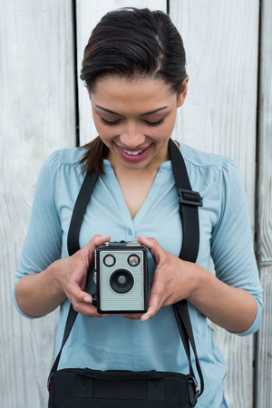 Female photographer with old fashioned camera against wooden background Stock Photo