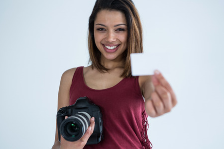 Portrait of female photographer showing visiting card in studio Stock Photo