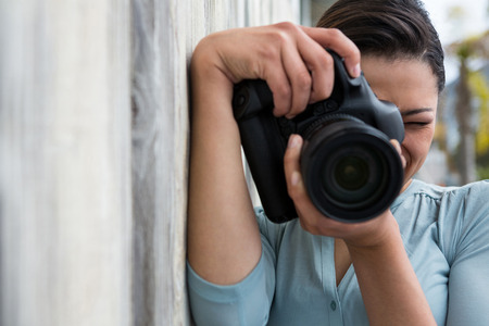 Close-up of female photographer with digital camera Stock Photo