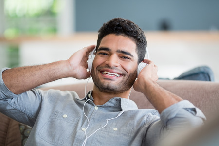 Portrait of man listening to music on headphones in living room at home