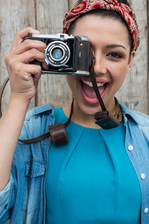 Portrait of female photographer with old fashioned camera against wooden background