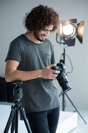 Male photographer reviewing captured photos in his digital camera at studio Stock Photo