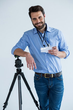 Portrait of male photographer showing identity card in studio